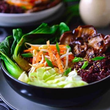 This forbidden rice bowl with bok choy, shiitake mushrooms, crispy vegetables and sesame-ginger sauce is all you need for an easy, healthy and filling vegetarian or vegan dinner.