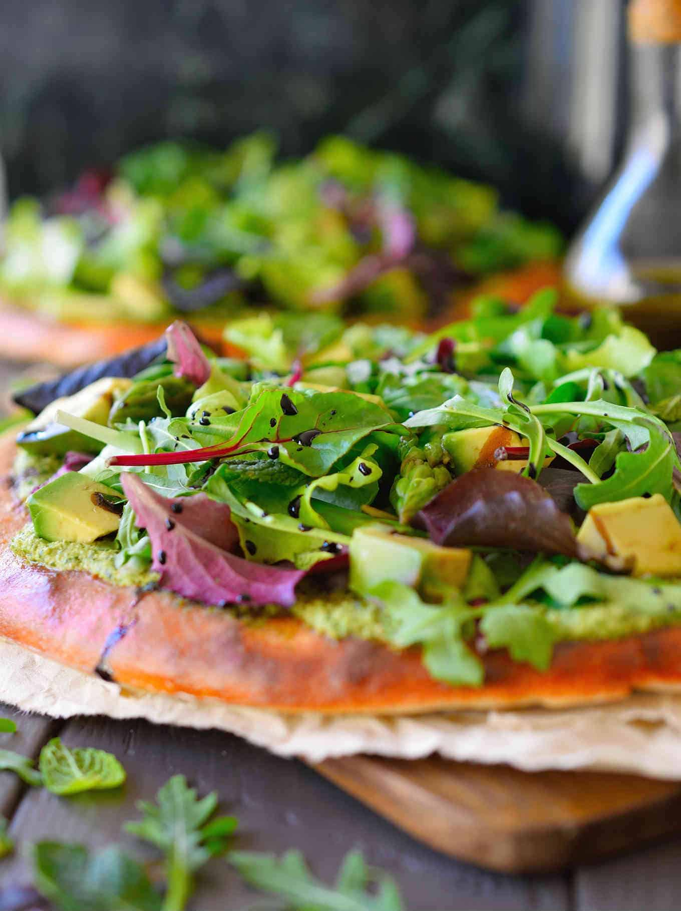 This recipe for green pizza with herbed vegan cashew cheese is a fresh and refreshing way to eat your greens. This vegan pizza recipe is packed with flavour but without the grease and looks beautiful on the plate with fresh baby greens, steamed asparagus, creamy avocado all sitting atop a delicious cashew cheese flavoured with cilantro, mint and lime. Best of all it comes together in just 20 minutes!