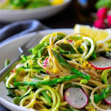 This spring vegetable zoodle pasta with garlicy lemon sauce is light and fresh and the perfect way to take advantage of the season's vegetables. Lightly blanched asparagus and snow peas are tossed with zucchini noodles and whole wheat pasta and topped with crispy radishes. A quick and easy recipe for a busy weeknight dinner.