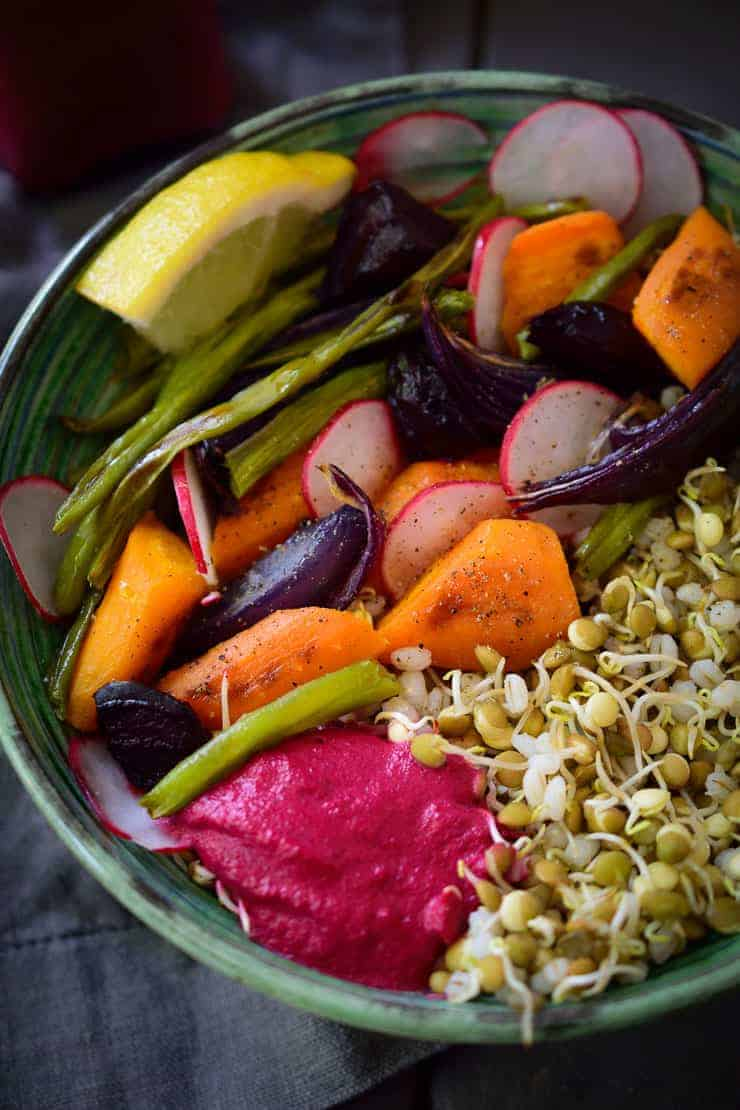 Sprouted lentil vegan Buddha bowl with roasted vegetables and a sweet and sour beet-tahini sauce.