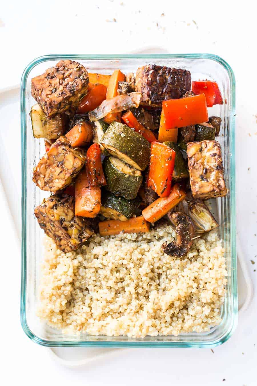 An overhead shot of quinoa, tempeh and veggies in a glass storage container.