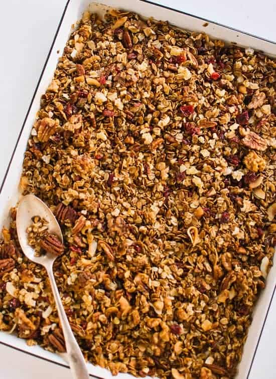 A pan of gingerbread granola with a spoon.