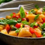 This vegan pumpkin gnocchi is easy to make with just a few simple ingredients. Served with a garlicky zucchini-red pepper sauce and fresh basil sprinkled on top, this colourful dish is a prime example of how simple is best!