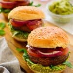 Three vegetarian sliders on a try with mint-pea pesto in a bowl.