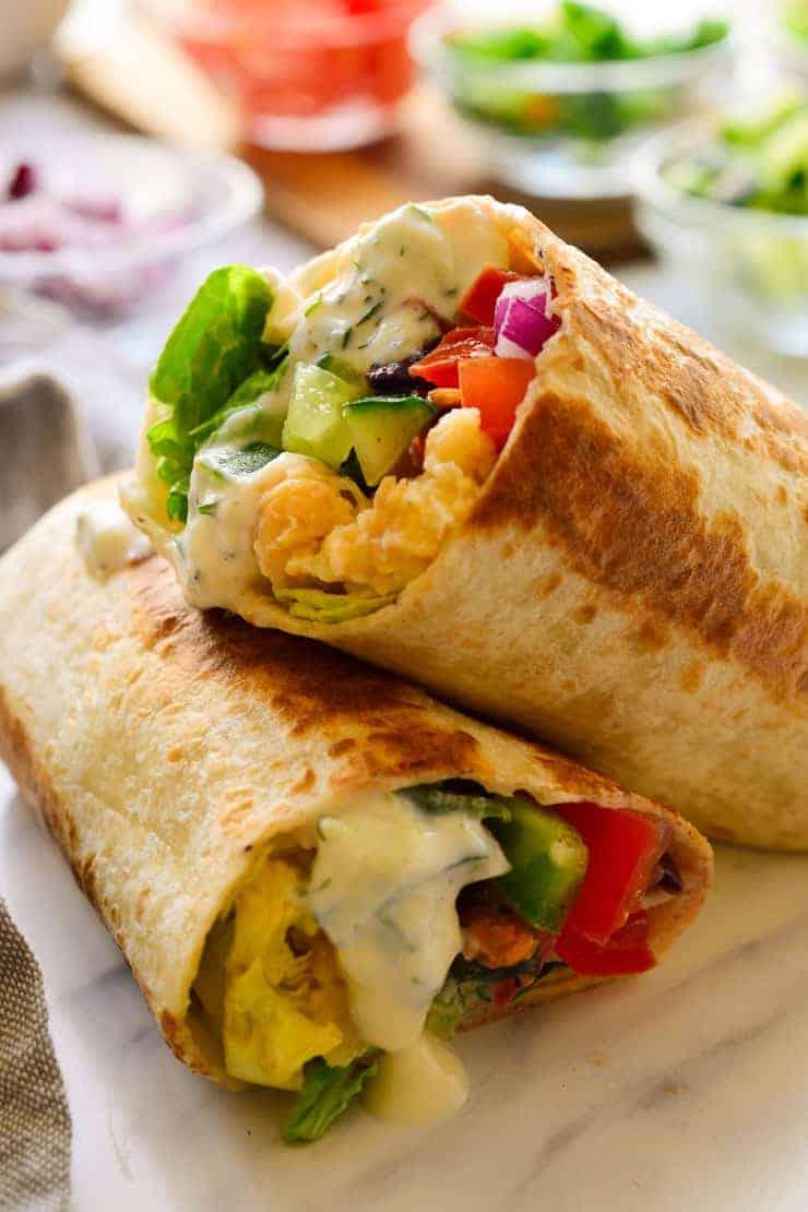 Vegan Mediterranean wraps cut in half with tzatziki sauce.
