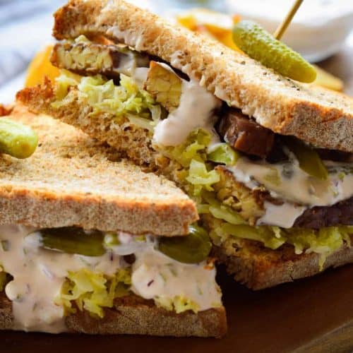 Vegan tempeh reuben sandwich on a serving board with a pickle on top.