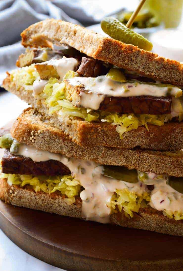 Vegan tempeh reuben sandwich stacked on a serving board.