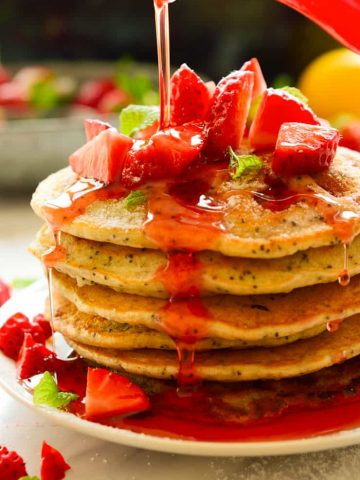 A stack of vegan strawberry pancakes with syrup being poured over.