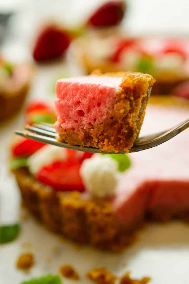 A slice of vegan strawberry mousse tart on a fork.