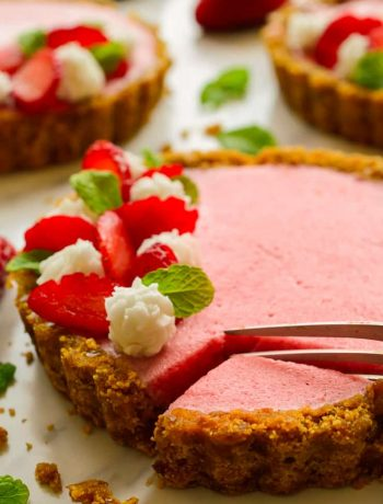 Vegan strawberry mousse tart with a fork taking a slice.