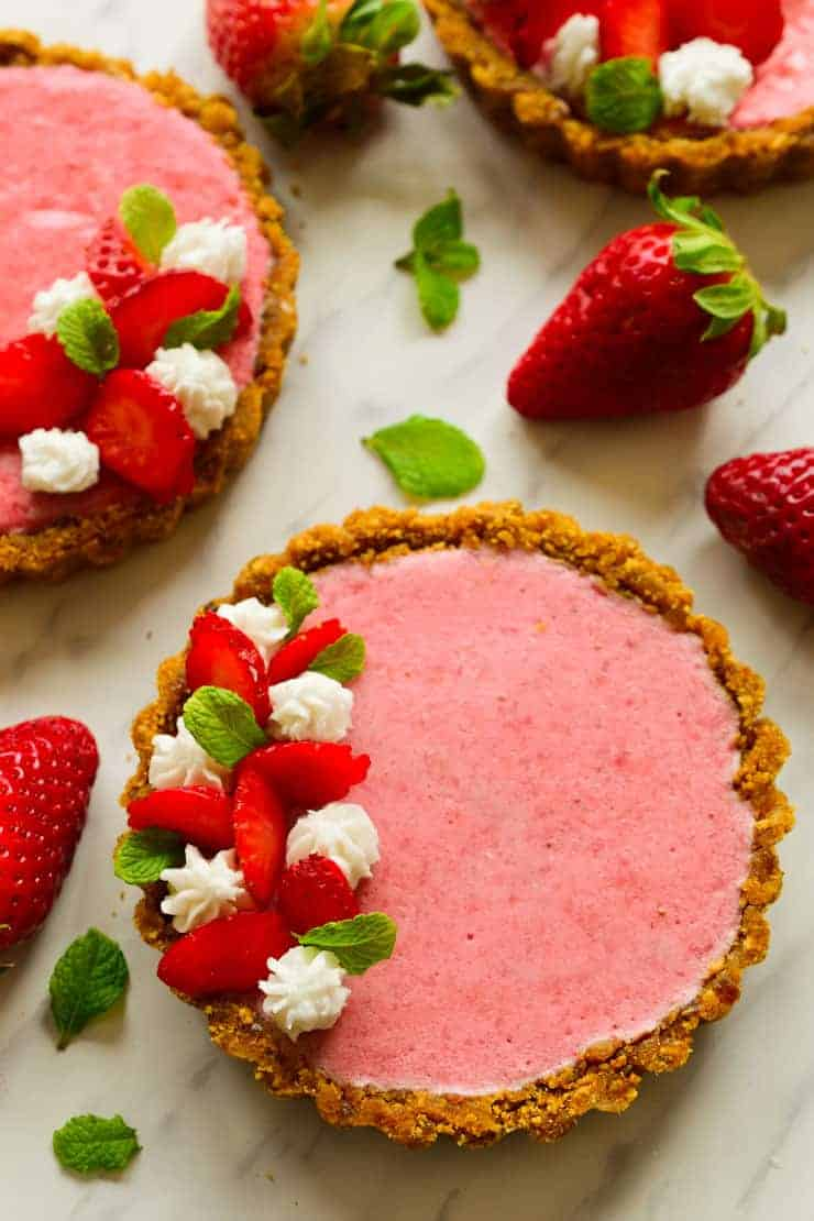 Vegan strawberry mousse tarts with coconut whipped cream and sliced strawberries seen from above.