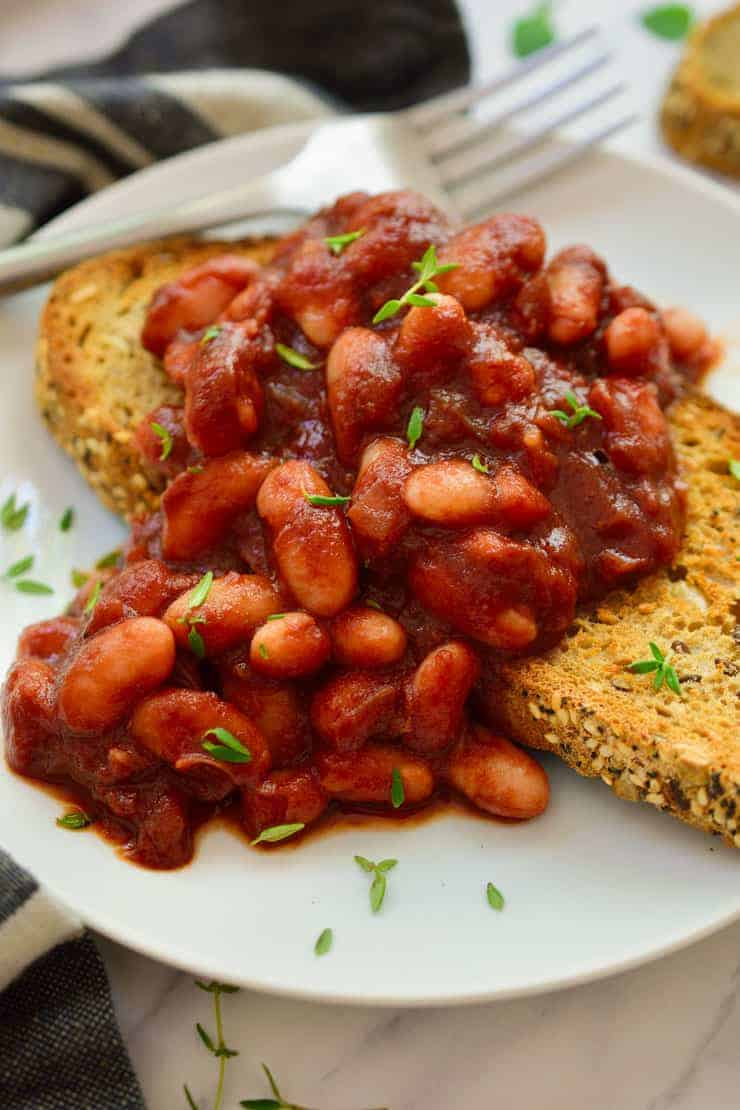 Smoky vegan beans on toast served on a plate.