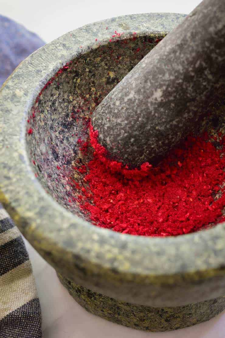 Freeze-dried raspberries crushed into a powder in a mortar and pestle.