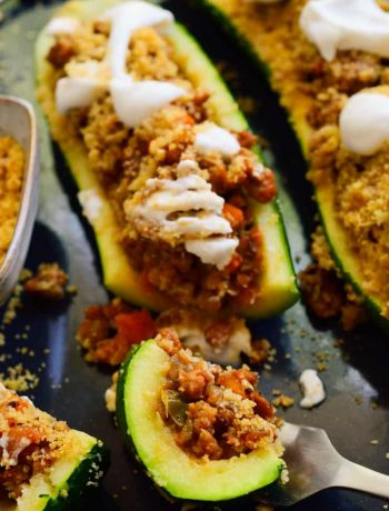 Vegan stuffed zucchini with breadcrumbs and sour cream on top.