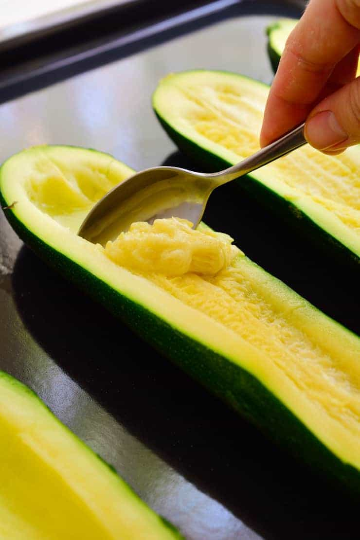 Scooping the pulp out of a zucchini with a spoon for vegan stuffed zucchini.