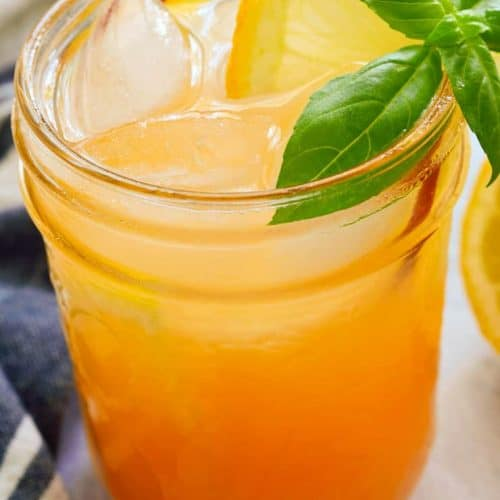 Peach nectar lemonade in a mason jar garnished with lemon and basil.