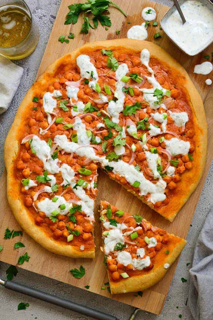 Spicy vegan buffalo chickpea pizza with ranch dressing seen from above.