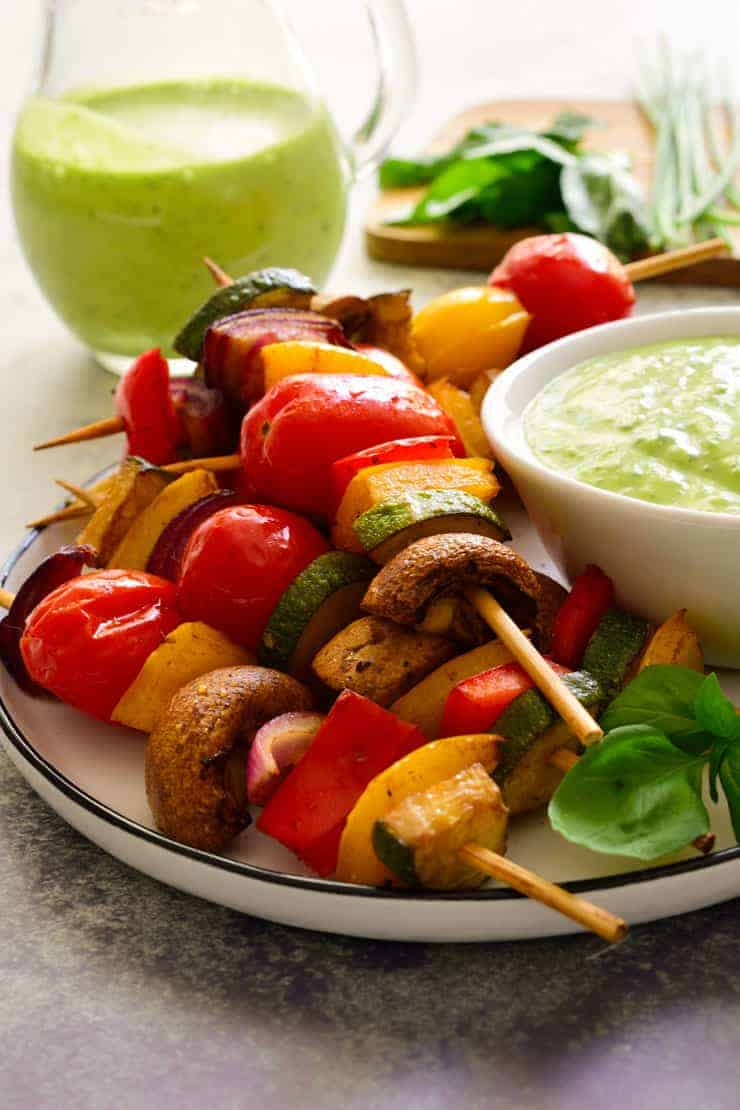 Veggie skewers on a plate with vegan green goddess dressing in a bowl.