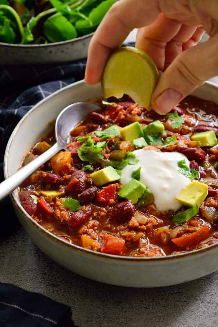 Squeezing a lime over vegetarian chili in a bowl.