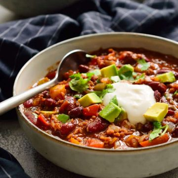 Vegetarian chili recipe in a bowl garnished with cilantro, vegan sour cream and avocado.