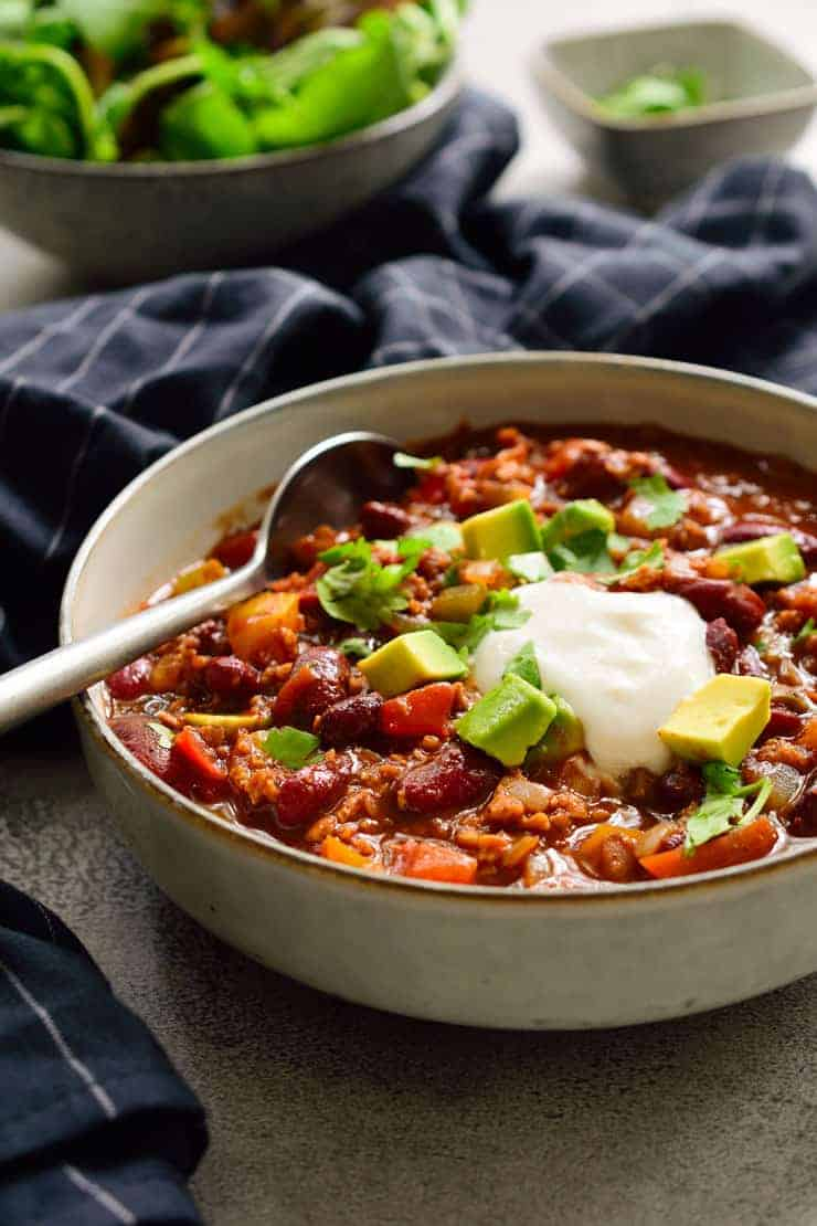 Vegetarian chili recipe in a bowl garnished with cilantro, vegan sour cream and avocado.