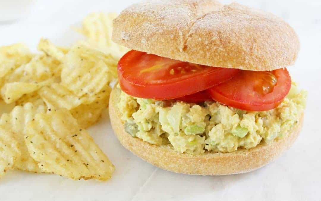 vegan chicken salad sandwich on a white plate with potato chips.