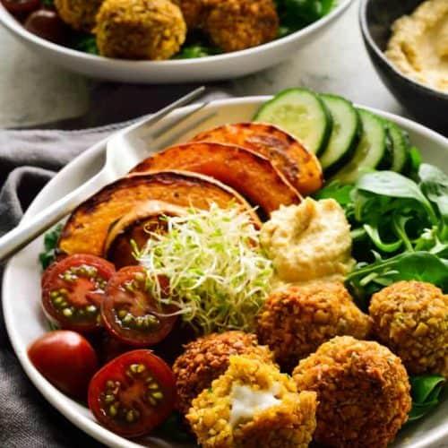 Feta-stuffed vegan falafel recipe in a bowl with veggies and hummus.