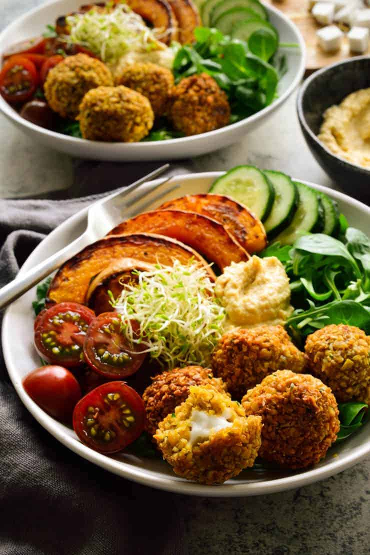 Feta-stuffed vegan falafel recipe in a bowl with veggies and hummus.