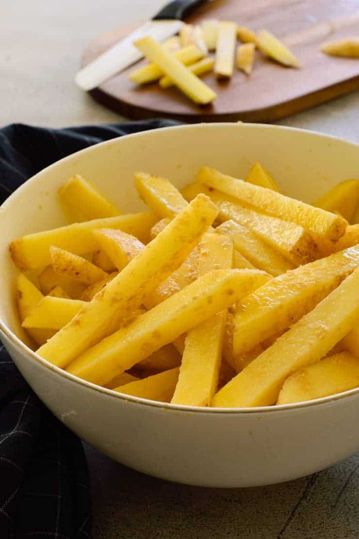 Potatoes cut into fries in a bowl.