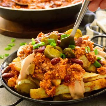 A plate of vegan chili fries with a fork