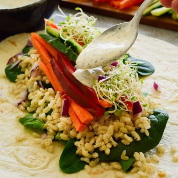 Ranch veggie wrap open on the table with ranch dressing dollopped over.