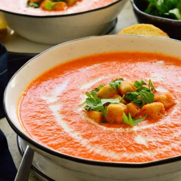 Two bowls of roasted red pepper soup garnished with croutons and chopped parsley.