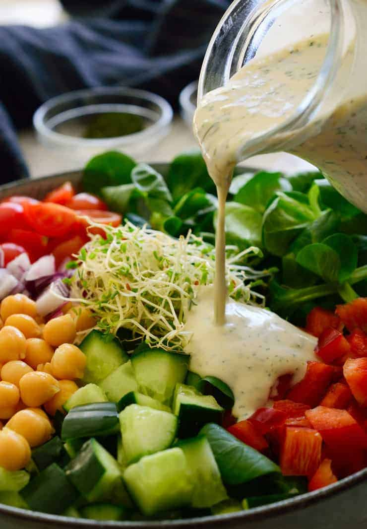 Pouring vegan ranch dressing over a big colourful salad.