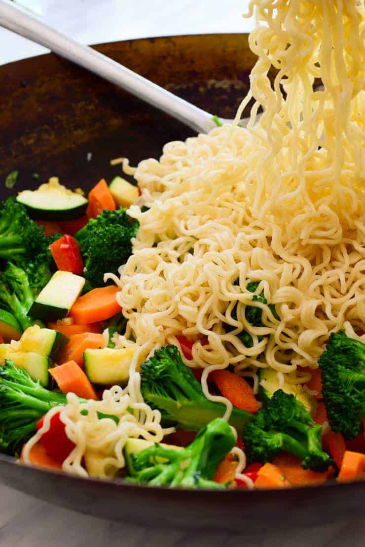 Tossing cooked ramen noodles into the wok with stir fried vegetables.