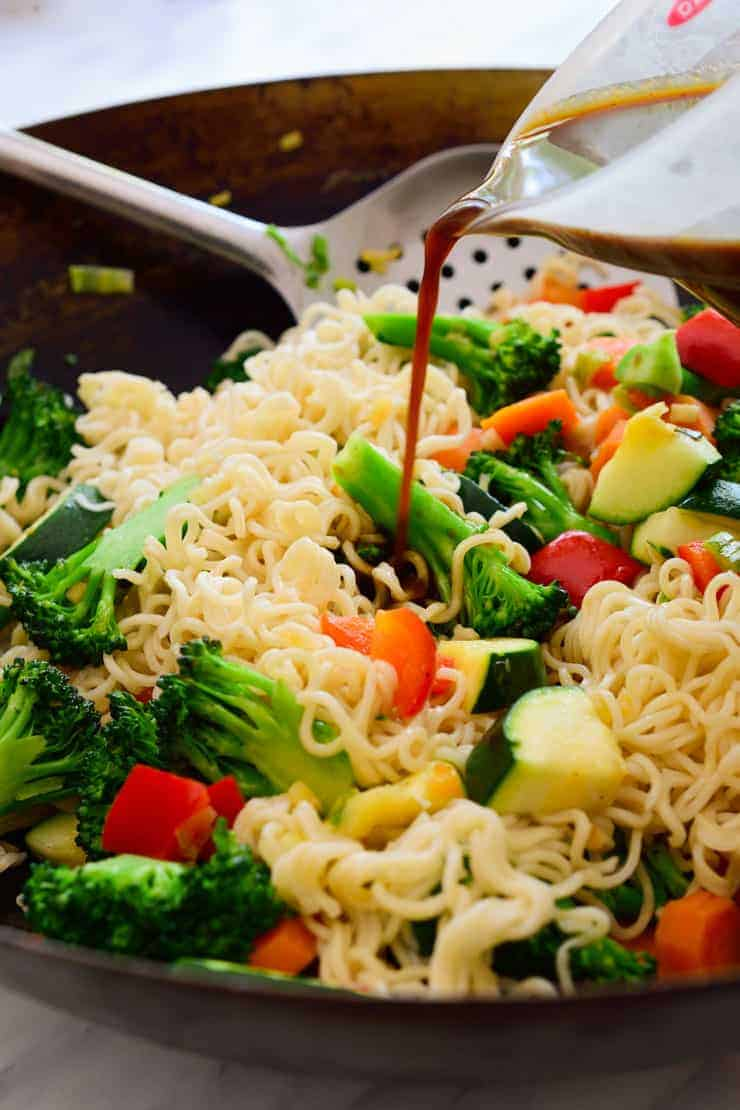 Pouring stir fry sauce over noodles and veggies in a wok.