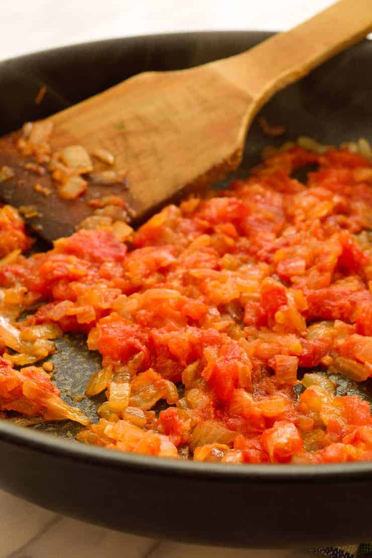Fried onions, garlic and tomato pulp in a pan.
