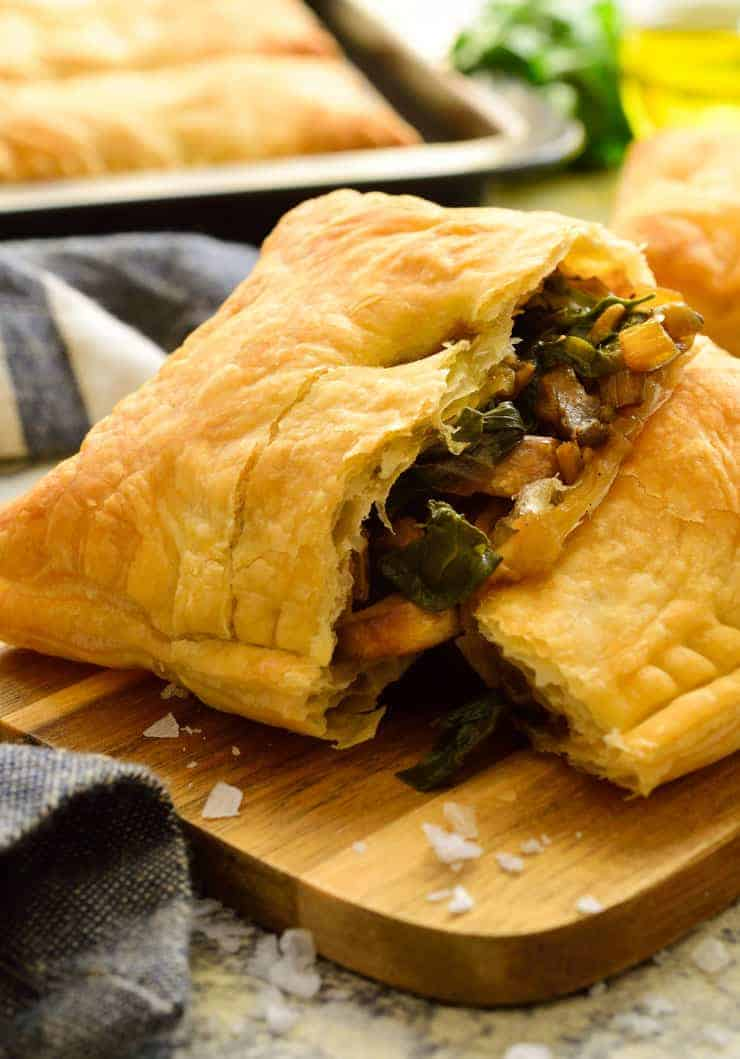 A puff pastry pocked pulled open on a cutting board exposing the chard and mushroom filling.