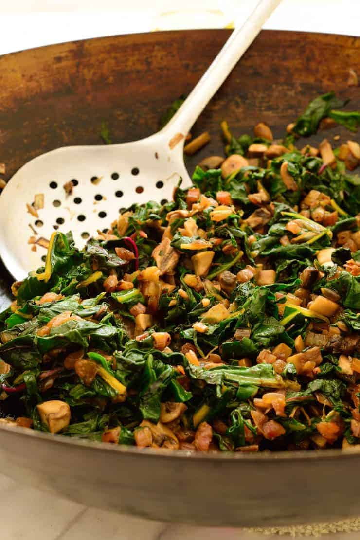 Swiss chard and mushroom filling in a large pan with a spoon.