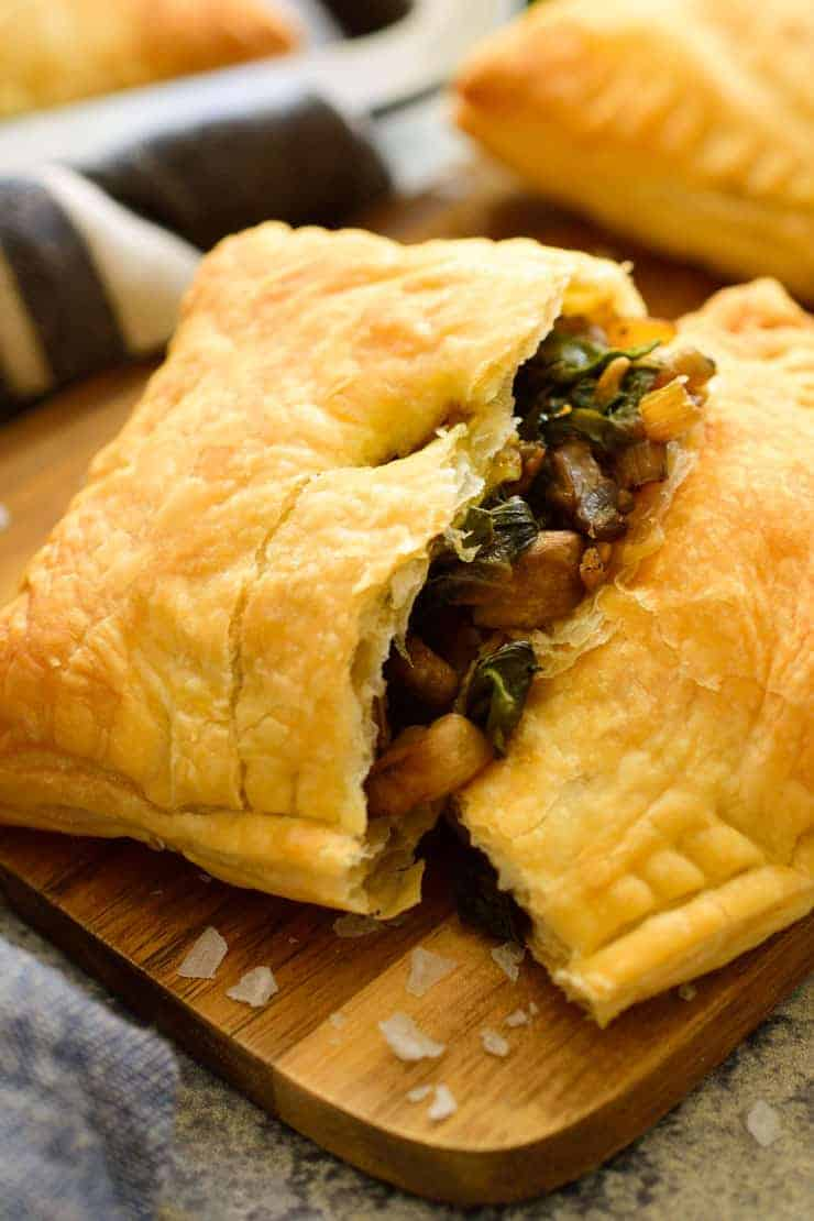 A close-up of an open Swiss chard and mushroom stuffed puff pastry.