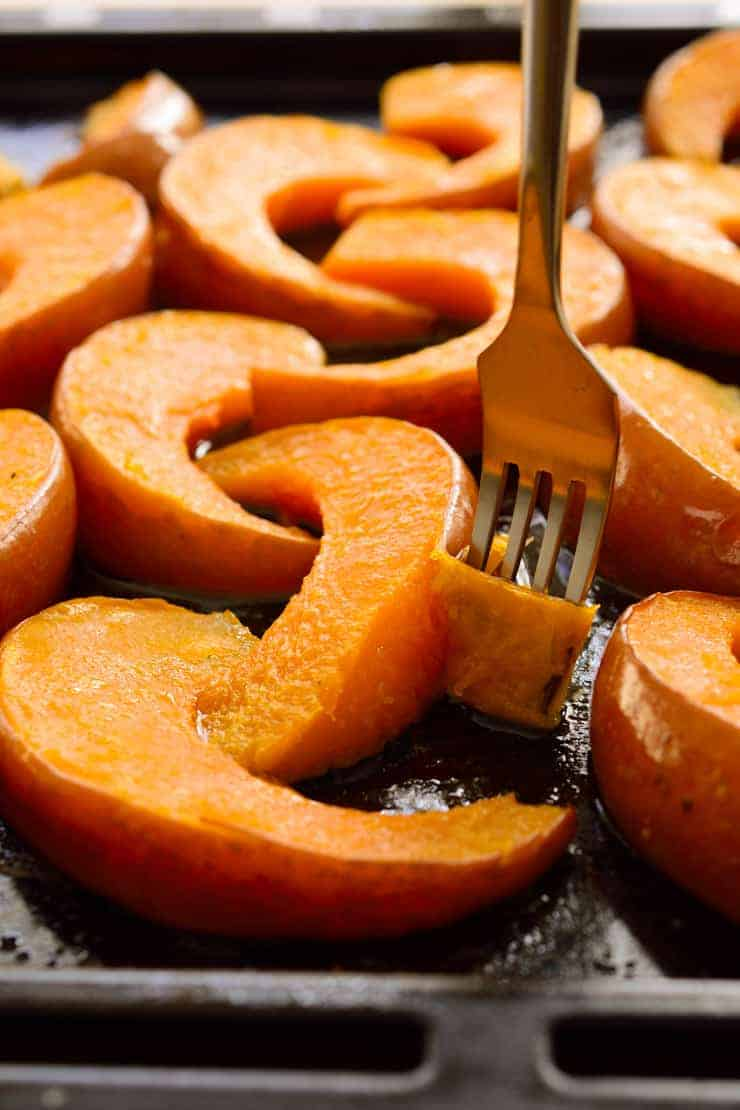 Peeling the skin off the roasted pumpkin with a fork.