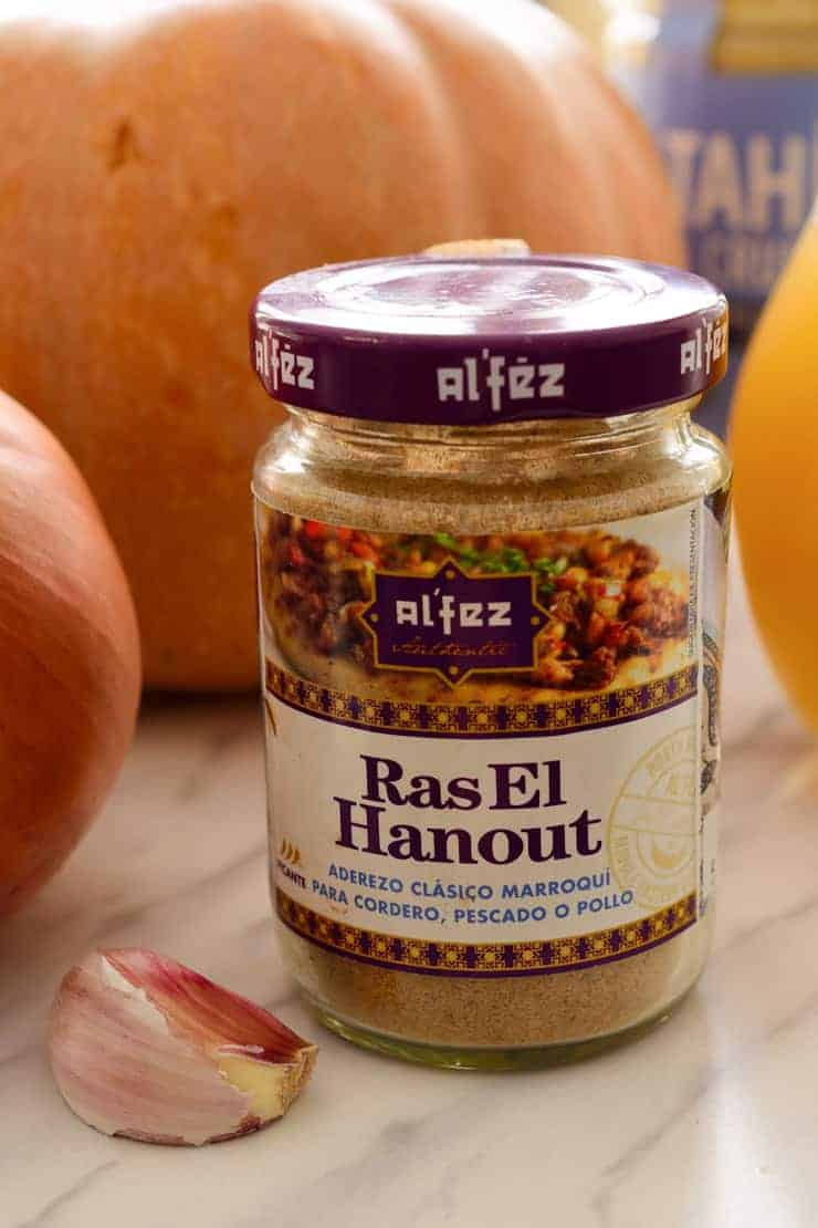 The raw ingredients for pumpkin tahini soup on a counter with a jar of ras el hanout in the front.