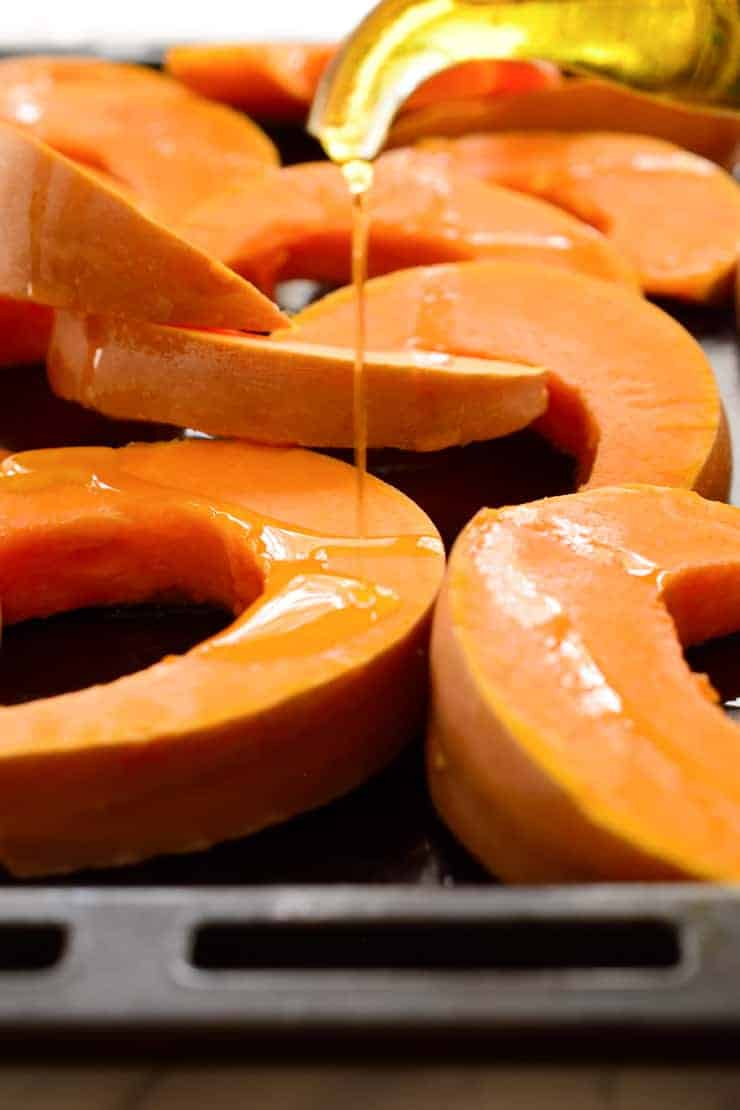 Drizzling olive oil over sliced pumpkin on a baking pan.