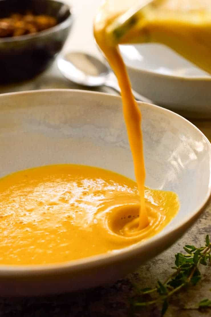 Pouring the pumpkin tahini soup from the blender into a white bowl.