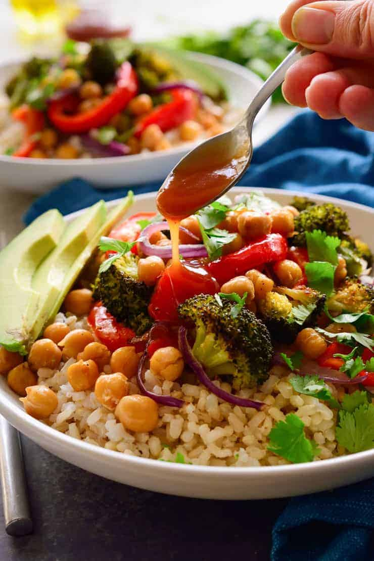 Drizzling BBQ sauce off a spoon onto brown rice, roasted veggies and chickpeas in a white bowl.