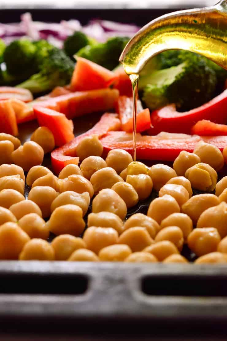 Drizzling olive oil over a pan of chickpeas and chopped veggies before roasting.