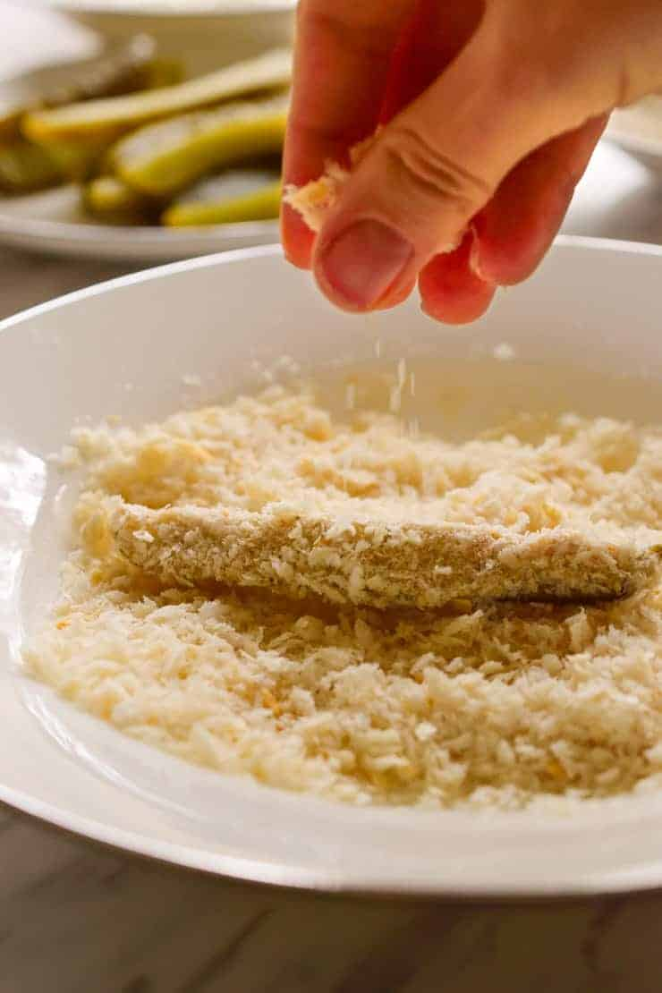 A slice of pickle in a bowl of panko breadcrumbs.