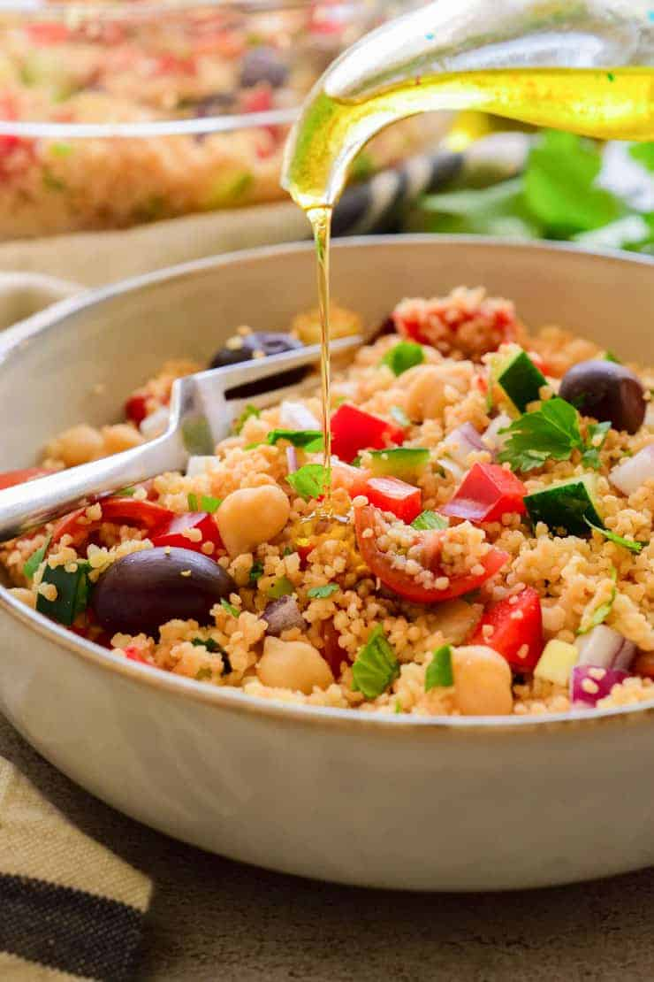 Drizzling olive oil over a bowl of vegan couscous salad.