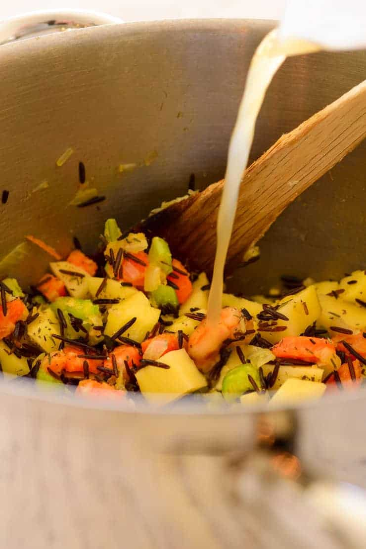 Pouring vegetable stock into the pot with the vegetables and wild rice.