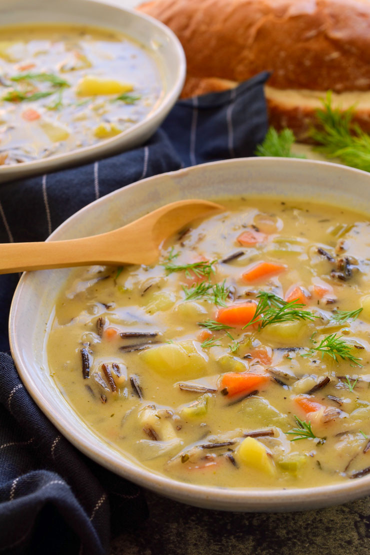 Two bowls of vegan wild rice soup with bread in the background.
