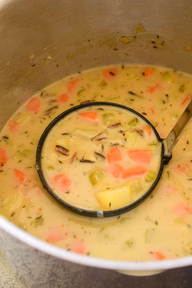 A ladle of wild rice soup in the pot.